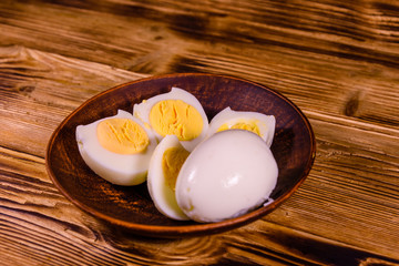 Ceramic plate with peeled boiled eggs on wooden table