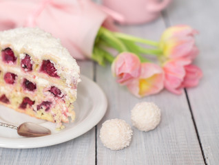 A cake with cherries and pink tulips on white wooden table