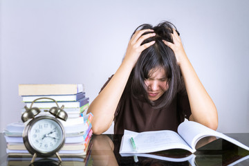 asian young girl reading a book preparing for exams,She shows headache, stress.