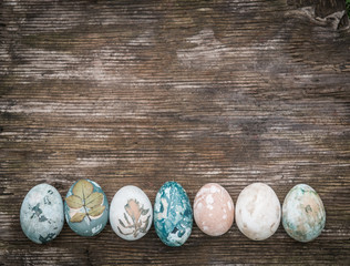 Easter greeting card, natural colored eggs over rustic wood and copy space