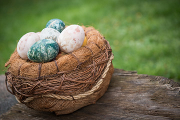 Basket with natural colored Easter eggs over green grass background
