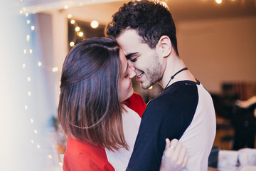 Cute and sensual young couple in love, smiling, hugging, cuddling and kissing inside house or apartment. Teenagers or millennials truly in love with each other, attractive boy and girl