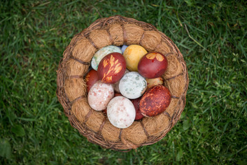 Top view of basket with Easter eggs over green grass