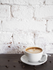Cup of cappuccino on wooden table with white brick wall background.