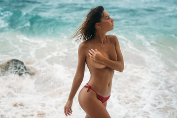 Portrait of sexy young girl in red swimsuit without bra posing on the beach. Beautiful brunette woman with long hair relaxing at the ocean. Concept of sporty model, swimwear, travel