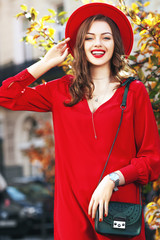 Beautiful happy smiling girl wearing stylish red hat, dress, wrist watch, with small green bag posing, walking in street. Outdoor portrait, natural day ligh.  Female autumn fashion concept