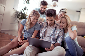 Group of friends sitting in sofa with laptop