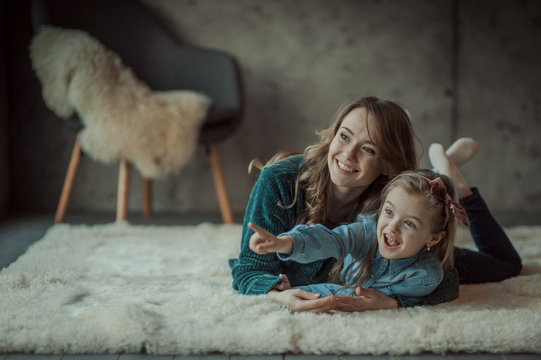 Smiling mother with her daughter in the room on the carpet