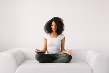 An African American young women sitting in the lotus position on white bed