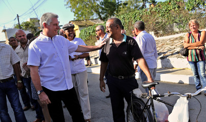 Cuba's First Vice-President Miguel Diaz-Canel talks to a local resident before casting his vote during an election of candidates for the national and provincial assemblies, in Santa Clara