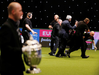 Security guards tackle protesters who entered the show ring during the awarding of the best in show during the final day of the Crufts Dog Show in Birmingham