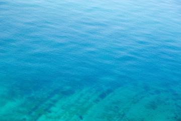 The texture of the water. Clear blue sea water with a stone slab on the bottom.