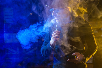 vaping man holding a mod, Vape. Men with beard in sunglasses vaping and releases a cloud of vapor.