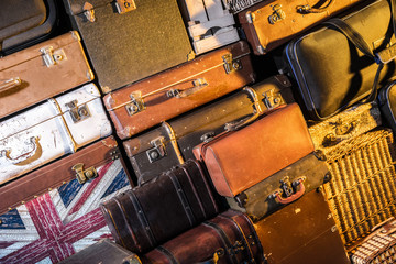 Wall of old suitcases. Many suitcases. Retro bags. Travel bags dumped in one heap.