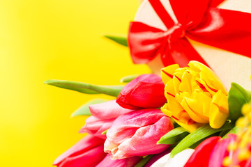 Colorful tulips flowers with decorartive giftbox on yellow background with free space. Mothersday or spring concept. Clos e up image