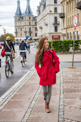 Asian woman walking in red fashion trench coat relaxing outside in Copenhagen city street, Denmark. Europe travel tourism tourist enjoying european lifestyle.