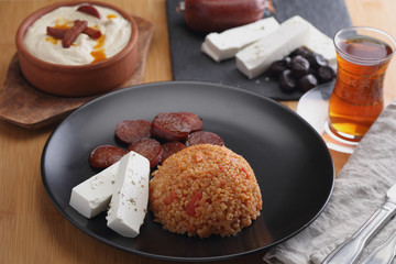 Turkish dinner with bulgur pilaf, sucuk, feta cheese, and hummus