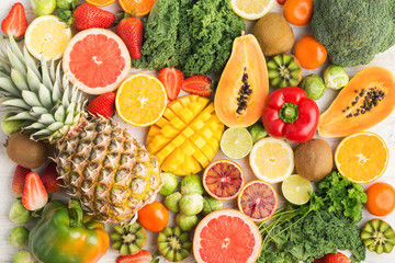 Fruits and vegetables rich in vitamin C background pattern, oranges mango grapefruit kiwi kale pepper pineapple lemon sprouts papaya broccoli, on white table, top view, selective focus