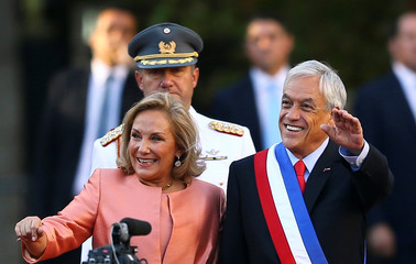 Chile's President Sebastian Pinera, accompanied by his wife and First Lady Cecilia Morel, waves to people at La Moneda Presidential Palace in Santiago, Chile