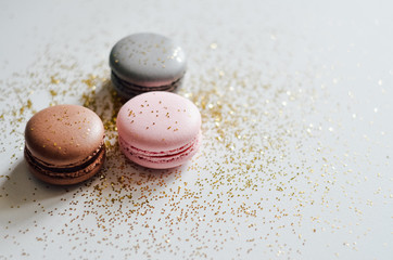 Pink, grey, brown macaroons with golden glitter on white background, copyspace, holiday concept