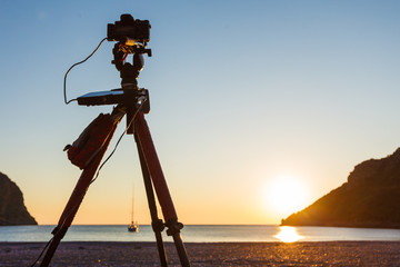 Camera taking picture of sunrise over sea surface
