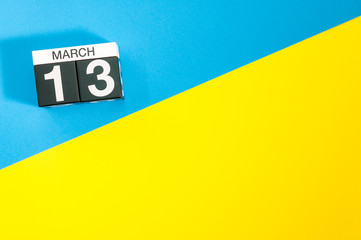 March 13th. Day 13 of march month, calendar on blue and yellow background flat lay, top view. Spring time. Empty space for text