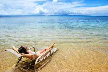Young woman in bikini lying in a sun chair on Taveuni Island, Fiji
