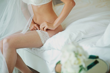 Beautiful bride model in white lace lingerie. Close-up of a female buttocks on the table. Girl in panties, belt, and stockings. Hosiery underwear. Portrait of sexy fashion woman