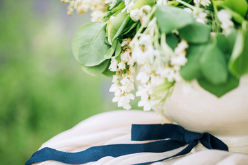 close-up vase with white flowers tied with blue ribbon against a background of meadow
