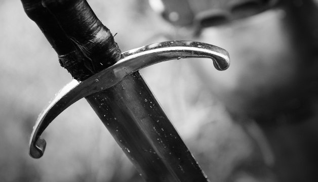 Medieval knight with sword in armor as style Game of Thrones in battle or tournament black and white old photo