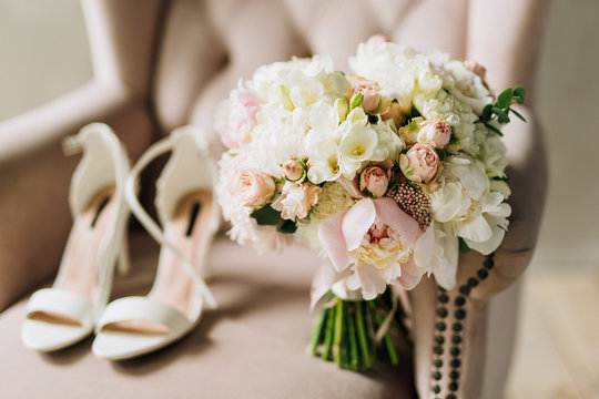 close-up of a wedding bouquet of white peonies, rose carnations which stands on a pink armchair against a background of wedding shoes