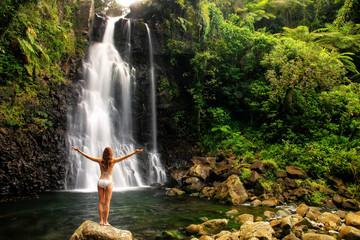 Young woman in bikini standing by Middle Tavoro Waterfalls in Bouma National Heritage Park, Taveuni Island, Fiji