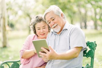 Happy senior Asian couple using tablet