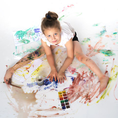 A little girl paints with paint and brush.