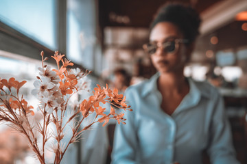 Plastic flowers in the foreground on a restaurant table and the portrait of young Brazilian girl in sunglasses in a defocused background behind flowers; teal and orange colors palette