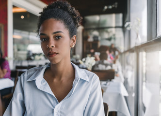 Close-up portrait of an appealing Brazilian girl sitting in a cafe next to the window; black young female in a striped shirt is sitting in a bar with people in a defocused background