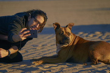 Young woman taking a photo with her smartphone with her American Staffordshire terrier dog on a beach