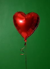 Single big  red heart balloon object for birthday party on green
