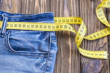 Healthy lifestyle and nutrition concept. Blue jeans with a measuring tape instead of a belt.