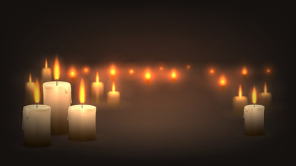 Many candles burn in the dark