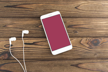 White smartphone with a pink color screen, headphones on a wooden background. music. the Internet.