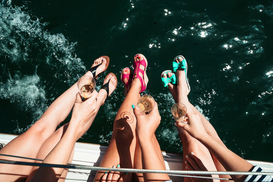 Woman, girl leg, legs in bright shoe, hills on boat, sailboat with glass of champagne. Ocean, fun, California