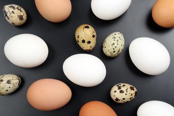 different chicken eggs lie randomly on dark background.