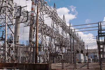 A high voltage electricity power sub station under a bright blue sky with white clouds