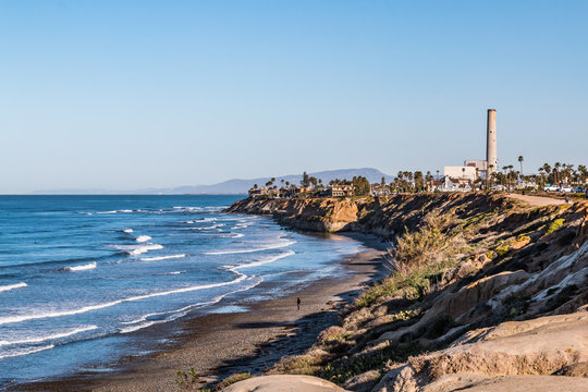 Man walks near cliffs on South Carlsbad State Beach in San Diego, California with the power plant landmark tower in the background.