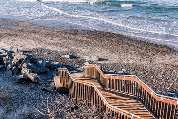 A staircase leading down to a stone-covered beach at South Carlsbad State Beach in San Diego, California.