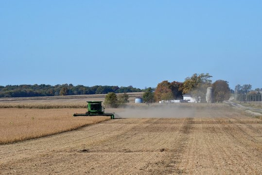 Combine harvesting soybeans with farm scene in background