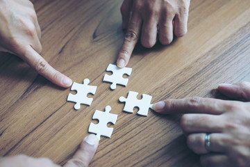 close up hand of group business partnership people puting together a jigsaw puzzle  , business teamwork Strategy concept