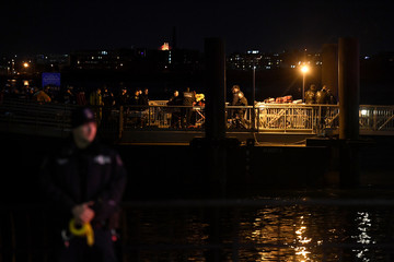 Rescue crews are seen on East 34th Street/Midtown East Landing after a chartered Liberty Helicopters helicopter crashed into the East River in New York