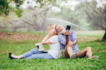 Elderly couple using a laptop while sitting on grass in the park